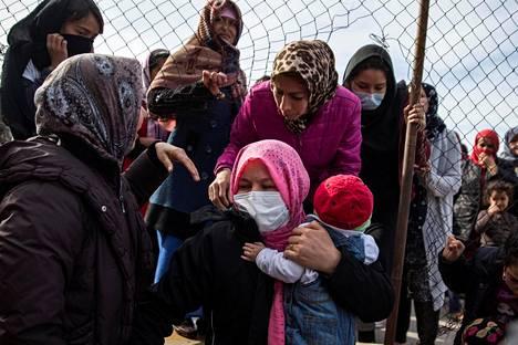 Afgaaninaiset pujottautuivat mielenosoituksen aikana aidassa olevan reiän läpi pakolaisleirillä Ateenassa Kreikassa maanantaina.