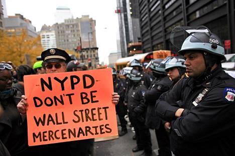 Kyltin teksti: Poliisit, älkää olko Wall Streetin palkkasotureita.