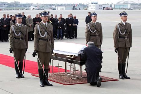 Laki ja oikeus -puolueen johtaja Jaroslaw Kaczýnski polvistui lentoturmassa kuolleen veljensä, Puolan entisen presidentin Lech Kaczýnskin arkun edessä huhtikuussa 2010.