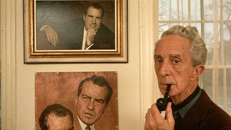 """Norman Rockwell smokes a pipe as he stands next his portraits of Richard Nixon in the Norman Rockwell Museum at the """"corner house"""" in Stockbridge, Massachusetts. Rockwell was an important documentarian of American life. (Photo by Jonathan Blair/Corbis via Getty Images)"""