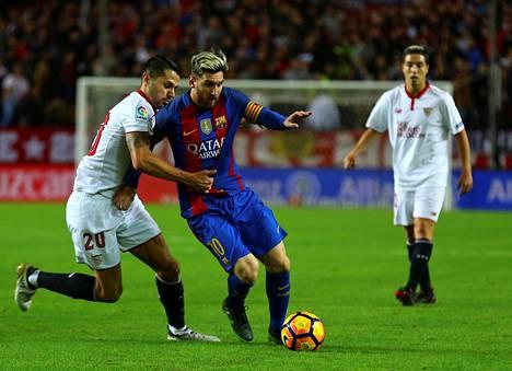 Sevillan laituri Vitolo yritti pysäyttää Barcelona-taituri Lionel Messin.