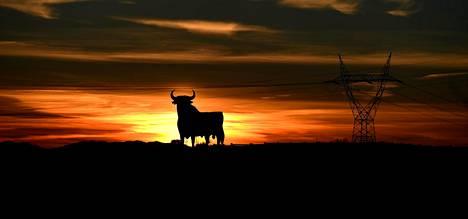 Laskeva aurinko paistaa härkää esittävän suuren tienvarsiteoksen takaa El Berrónissa Asturiassa. Aurinko laskee Keski-Euroopan aikavyöhykkeen alueista viimeisenä juuri Luoteis-Espanjassa.