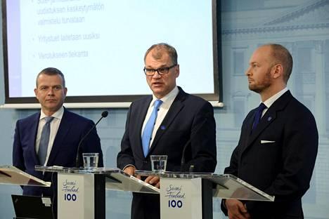 Trioon kuuluvat hallituspuolueiden puheenjohtajat eli kokoomuksen valtiovarainministeri Petteri Orpo, keskustan pääministeri Juha Sipilä ja sinisten eurooppa-, kulttuuri ja urheiluministeri Sampo Terho.