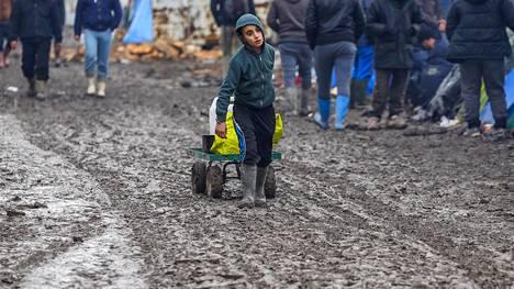 Pakolaislapsi vetää tavaroitaan kärryssä pakolaisleirillä Calais'n lähistöllä helmikuussa 2016.