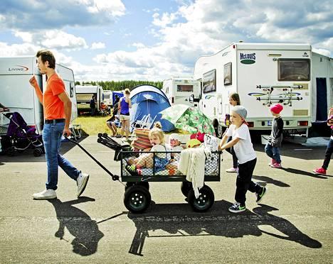 Tamperelainen Lauri Vähäjylkkä vetää perhettään kohti asuntovaunua. Kyydissä vasemmalta Clara, Olga, Ralf (keltainen hattu) ja Rudolf (punainen hattu). Työntämisessä auttaa Frans.
