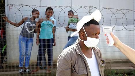 Jika Joen hökkelikylässä Pietermaritzburgissa asuvan miehen lämpöä mitattiin, kun lääkintöhenkilöstö selvitteli alueen asukkaiden kuntoa torstaina.