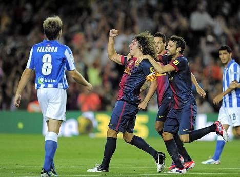FC Barcelonan kapteeni Carles Puyol (kesk.) sai onnitteluja joukkuetoveriltaan Cesc Fabregasilta (oik.) tehtyään maalin ottelussa Real Sociedadia vastaan Barcelonassa sunnuntaina.