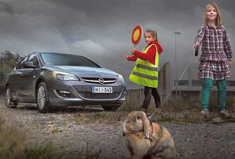 Opel Astra on pysäytetty, kun Emma Peltola taluttaa kääpiöluppakania tien yli. Alli Mitchell ohjaa liikennettä. Lisää Kimmo Taskisen toisenlaisia autokuvia HS.fi/autot.