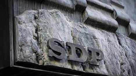 Sdp:n metallinen logo Puoluetoimiston seinässä Hakaniemessä.