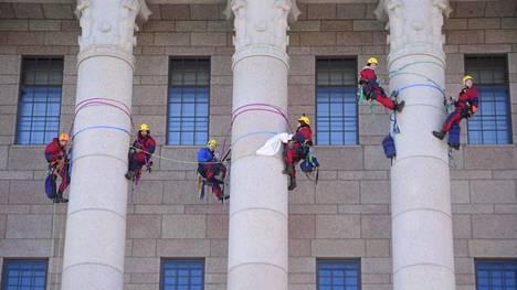 Eduskuntatalon pylväisiin kiipesi vajaat kymmenen ihmistä, jotka olivat pukeutuneet ympäristöjärjestö Greenpeacen haalareihin Helsingissä maaliskuussa 2019.