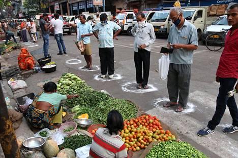 Vihanneskaupoille tulleet ihmiset odottivat vuoroaan maahan piirrettyjen ympyröiden sisällä välttääkseen lähikontaktia Intian Kolkatassa keskiviikkona.