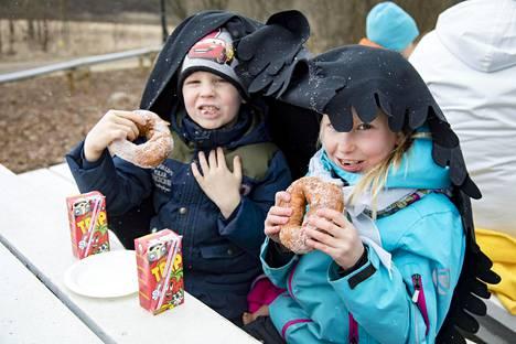 Elia, 5, (vas.) ja Linnea, 7, Ursinus söivät munkit lumisateessa viltin alla.