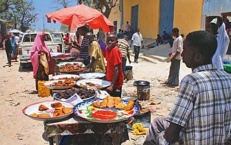 Katukauppiaat myivät ruokaa leppoisissa merkeissä Hamarweynen torilla Mogadishussa maaliskuun lopulla.
