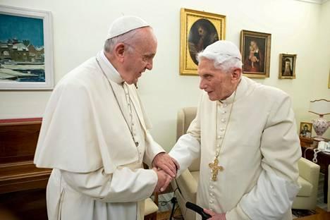 Paavi Franciscus (vasemmalla) ja emerituspaavi Benedictus XVI kättelemässä joulukuussa 2018.