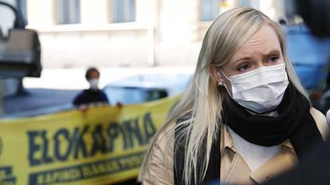 Sisäministeri Maria Ohisalo vastasi tiedotusvälineiden kysymyksiin Säätytalon edustalla maanantaina. Elokapina-liike osoitti mieltään Ohisalon takana.