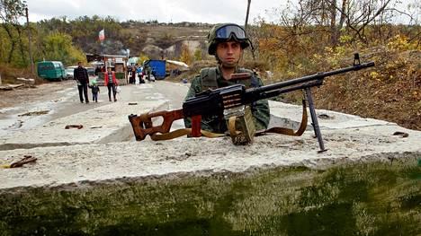 Sotatoimet Itä-Ukrainassa jatkuvat. Luhanskin alueen separatistien sotilas vartioi tiesulkua viime viikonvaihteessa.