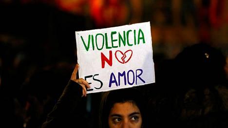 """Mielenosoittajan kyltissä luki """"Väkivalta ei ole rakkautta"""" kesäkuun alussa Buenos Airesissa."""