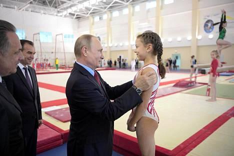 Venäjän presidentti Vladimir Putin tervehtii voimistelijatyttöä vierailullaan Krasnodarin harjoituskeskuksessa Venäjän Mustanmeren alueella tiistaina.