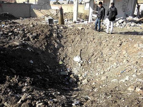Miehet katsovat Syyrian ilmavoimien iskun aiheuttamaa kuoppaa Ras al-Ainissa Hasakan maakunnassa.