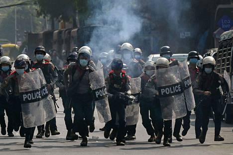 Poliiseja hajottamassa mielenosoitusta Yangonissa Myanmarissa lauantaina.