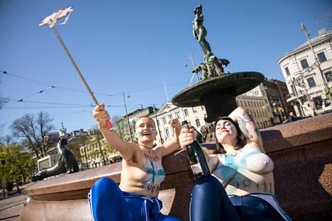 Sandra Marins (vas) ja Säde Vallarén nauttivat kesäisestä säästä Havis Amandan patsaalla.