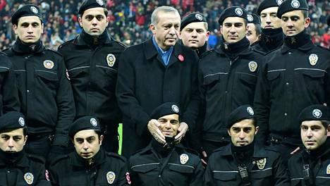 Presidentti Recep Tayyip Erdoğan poseerasi poliisien keskellä jalkapallo-ottelun yhteydessä 22. joulukuuta Istanbulissa.