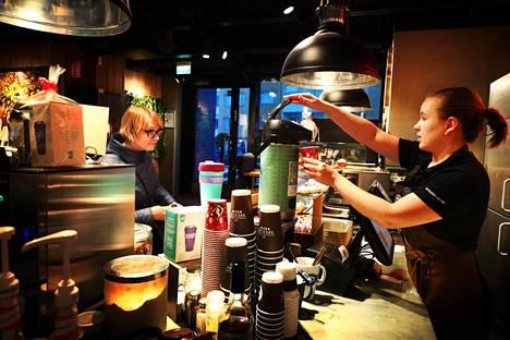"""Kirsi Siltanen osti kahvinsa Lauttasaaren Espresso Housesta kortilla niin kuin yleensäkin. """"Käytän käteistä vain jossain lasten urheilutapahtumissa, mutta niissäkin on aika usein jo Mobile Pay käytössä."""" Maksun otti vastaan barista Riina Nieminen."""