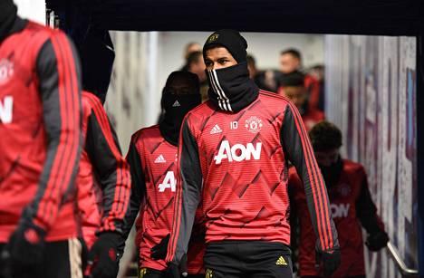 Manchester Unitedin Marcus Rashford asteli Tapaninpäivänä Burnleyn kentälle kauluri kasvojen suojana.