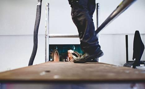 """Kuvataideakatemiassa on myös kesän aikana tehty sisäilmaan liittyviä korjauksia. Sami Lång teki viime viikon lopulla jäähdytyspalkiston vuosipuhdistusta. Takaseinällä on Nuutti Koskisen työ """"Hanasaari 1""""."""