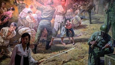 Pohjoiskorealaisessa museossa opas esittelee propagandataulua Korean sodasta.