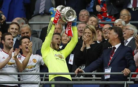Manchester United maalivahti David De Gea nostamassa cupin pokaalia.