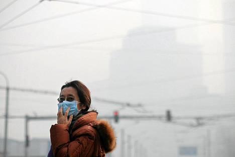 Kasvosuojaimella saasteita vastaan varustautunut nainen Pekingissä tammikuussa 2014.