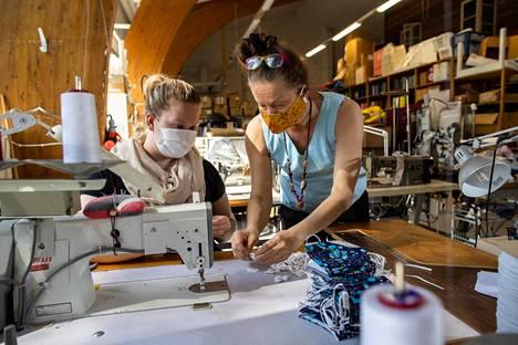 Janina Alanko (vasemmalla) ja Globe Hopen toimitusjohtaja Seija Lukkala tarkastelevat materiaaleja yrityksen ompelimossa Nummelassa, jossa valmistetaan nyt myös kasvomaskeja.
