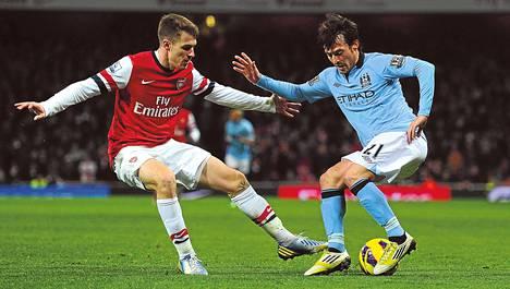 Manchester Cityn David Silva (oik.) yritti harhauttaa Arsenalin Aaron Ramseyn tammikuun liigaottelussa.