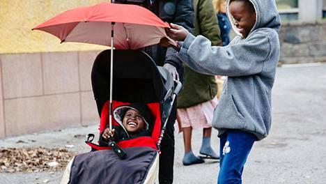 Kaksivuotias Alek Khot Biowei pääsi ajelemaan lastenrattailla, jotka ruotsalaisperhe on lahjoittanut pakolaisperheelle. Sisko Aguil Bior Deng, 8, auttoi sateenvarjon virittelyssä.