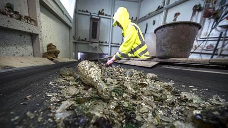 Ülle Fedulajeva perkaa Suomesta tulleesta jätelasista kankaita ja keramiikan paloja Viron Järvakandissa.