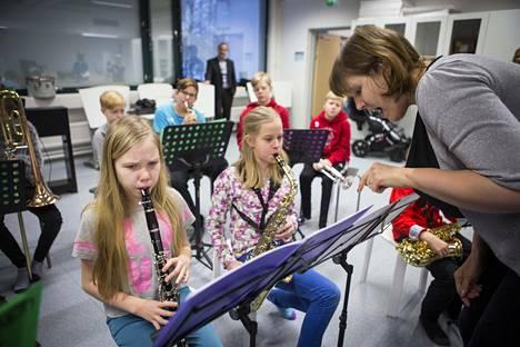 Helka Tamminen ja Hilla Ruotsala ovat valinneet soittimiksi klarinetin ja saksofonin. Stina Myllys opastaa.