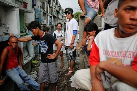 Sukulaiset ja ystävät odottelevat kahden serkuksen arkkujen saapumista hautuumaalla Manilassa Filippiineillä. Naamioidut asemiehet surmasivat serkukset kotinsa lähettyvillä.