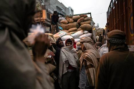 Intialaiset työntekijät valmistautuivat kuorma-autojen purkamiseen torilla  New Delhissä varhain keskiviikkoaamuna.