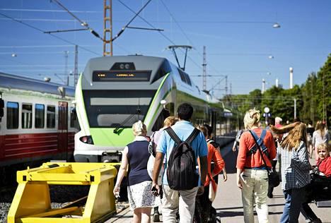 Matkustajia rautatieasemalla Helsingissä.