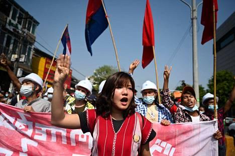 Mielenosoittajat nostivat kolme sormea protestiksi lauantaina Yangonissa.