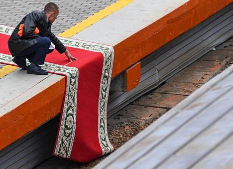 Työntekijä levitti punaista mattoa rautatieaseman laiturille ennen Kim Jong-unin saapumista Vladivostokiin.
