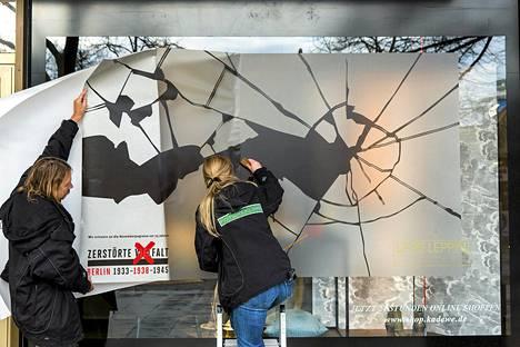"""Berliiniläisen tavaratalon ikkuna koristeltiin rikkoutunutta lasia esittävillä teippauksilla """"kristalliyön"""" muistopäivää varten. Marraskuun 10. päivän vastaisena yönä vuonna 1938 natsit hyökkäsivät suunnitellusti juutalaisia vastaan ympäri Saksaa. Aamulla katuja peittivät juutalaisten omistamien liikkeiden ja synagogien rikottujen ikkunoiden sirpaleet."""