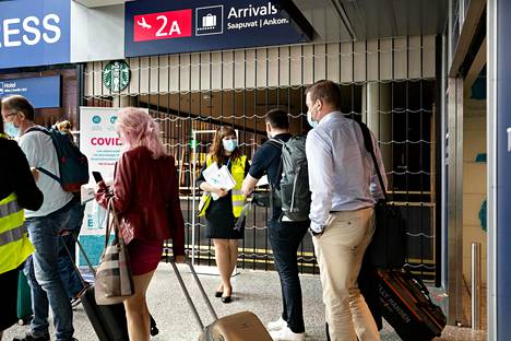 Finavian palveluneuvoja Sofia Koskinen jakoi koronavirusohjeistusta Helsinki-Vantaan lentoasemalle saapuville matkustajille tiistaina.