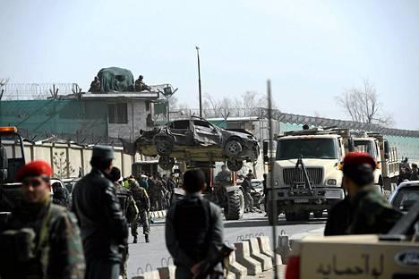 Afganistanilaissotilaat nostivat itsemurhaiskussa tuhoutunutta autoa Afganistanin puolustusministeriön pääportilla Kabulissa.