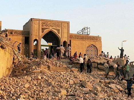 Ihmiset katselivat tuhotun pyhätön raunioita Mosulin kaupungissa Irakissa torstaina.