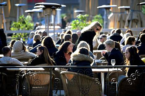 Ihmiset nauttivat kevätauringosta ilman maskeja ravintolan terassilla Tukholmassa maaliskuun lopulla.