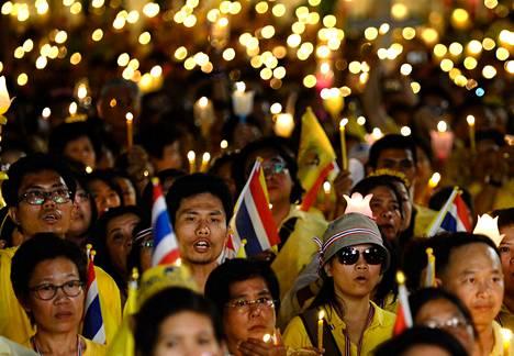 Keltaiseen eli opposition tunnusväriin pukeutuneet thaimaalaiset sytyttivät kynttilöitä ja rukoilivat kuninkaan syntymäpäivän kunniaksi Demokratian muistomerkillä Bangkokissa torstaina.