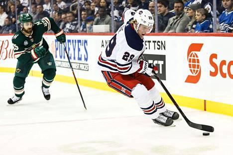Winnipeg Jetsin Patrik Laine luisteli kiekon kanssa Minnesota Wildin puolustajan Greg Pateryn edessä 26. helmikuuta 2019.