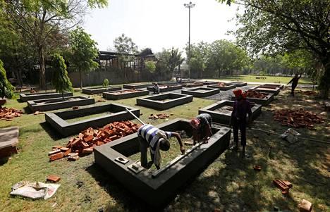Koronakriisin keskellä New Delhin kaupungissa Intiassa työntekijät rakensivat alustoja vainajien polttohautaukseen.
